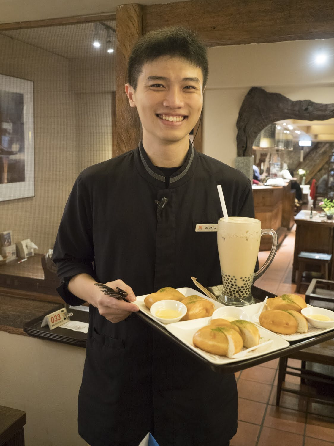 smiling waiter with tray and bubble tea